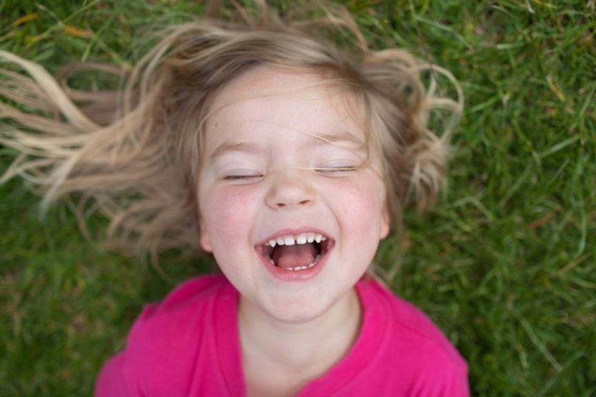 Child laughing while laying in the grass