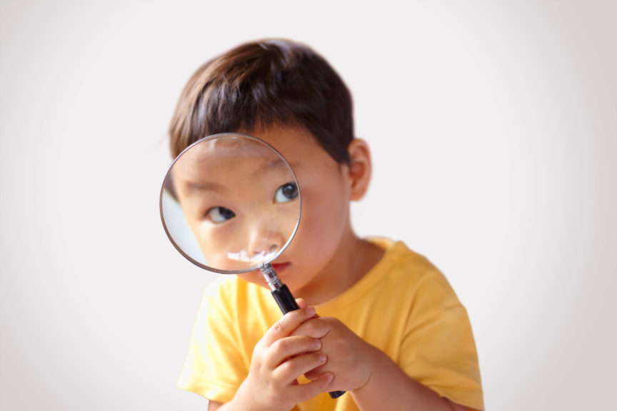 Child looking into a magnifying glass