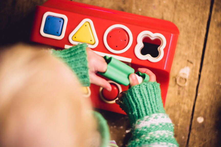child playing with shape board