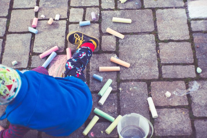 child-playing-with-sidewalk-chalk-outside