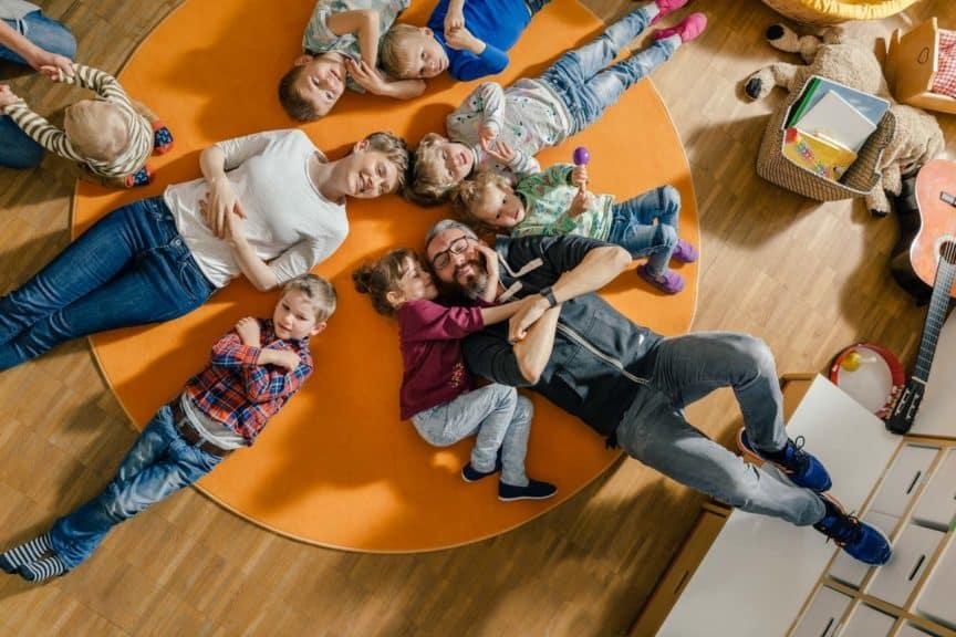 Children and teachers lying on carpet in kindergarten