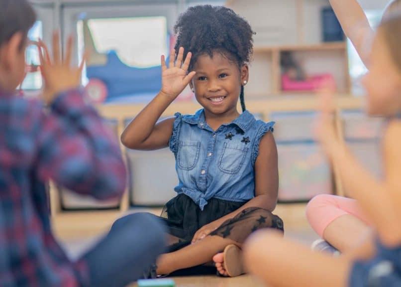 Children waving in kindergarten class