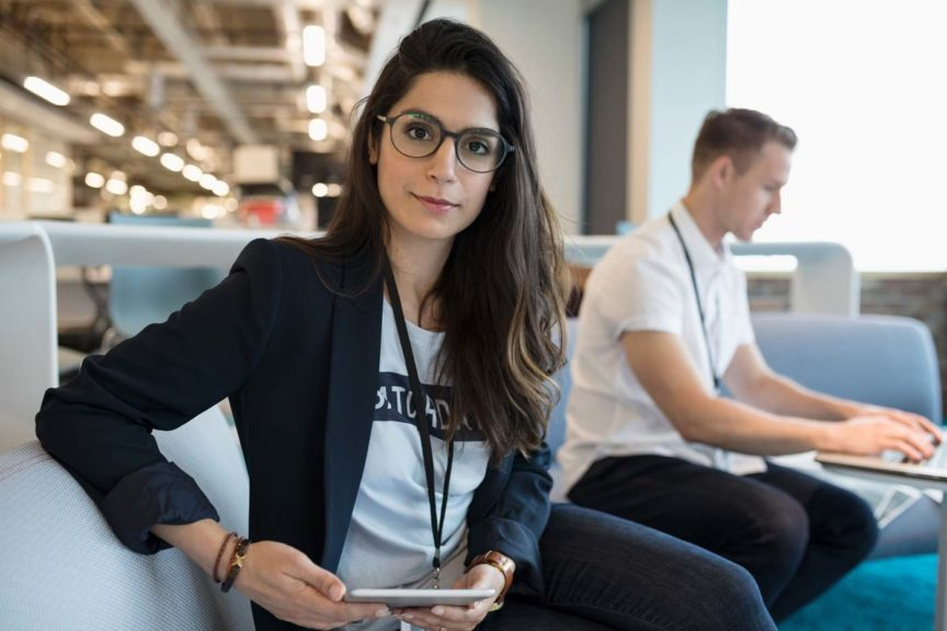 Portrait confident creative businesswoman using digital tablet in office lounge