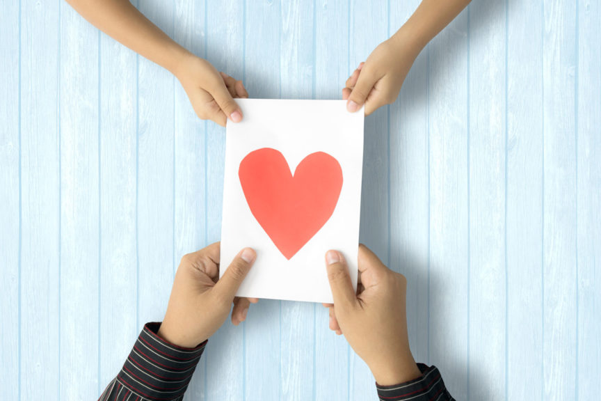 Couple Holding Paper With Heart Shape On Table