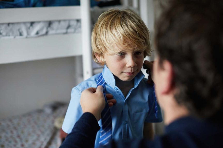Father helping his son get ready for school by tying is school tie