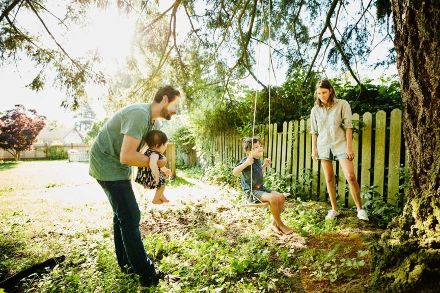 Family hanging out together at swing in backyard on summer morning