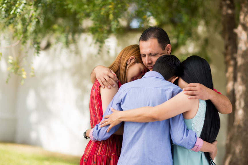 family praying and embracing outdoors