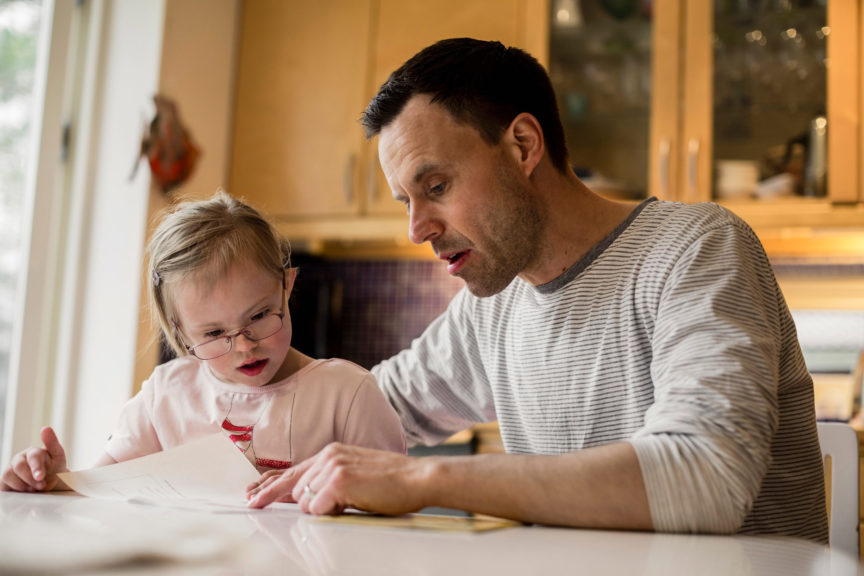 Father assisting handicapped daughter in studying at home