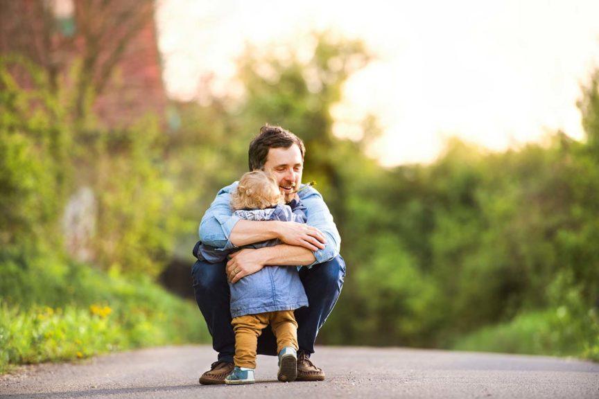 father hugging little boy