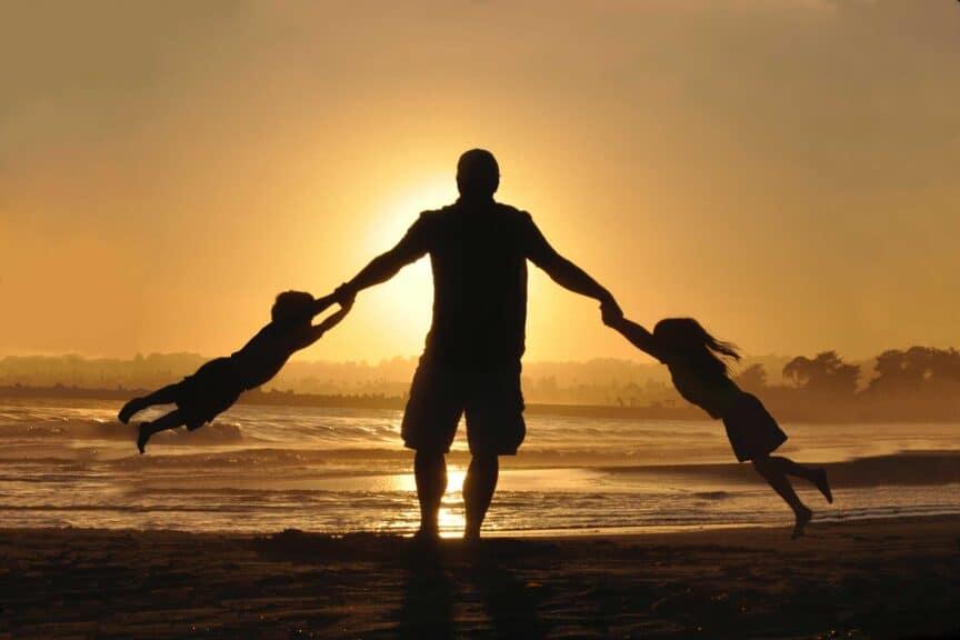 father-kids-beach-ocean-sunset-shadows