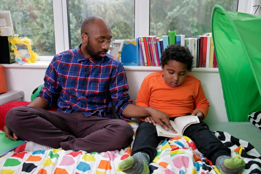 Father listening to son reading in bedroom