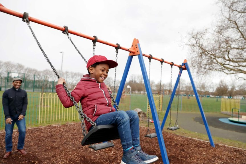 Father pushing son on swing at the park