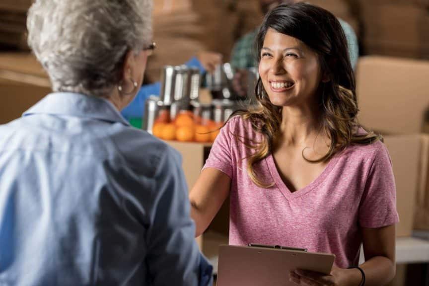 food-bank-organizer-greets-senior-volunteer