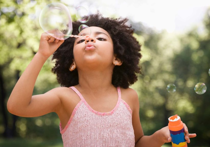 girl blowing bubbles outside