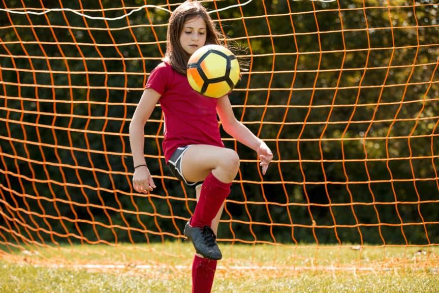 Girl bouncing soccer ball on kne