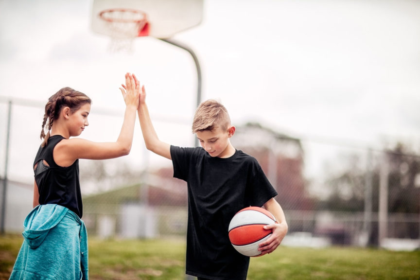 pre-teen boy and girl giving each other a high-five after basketball game