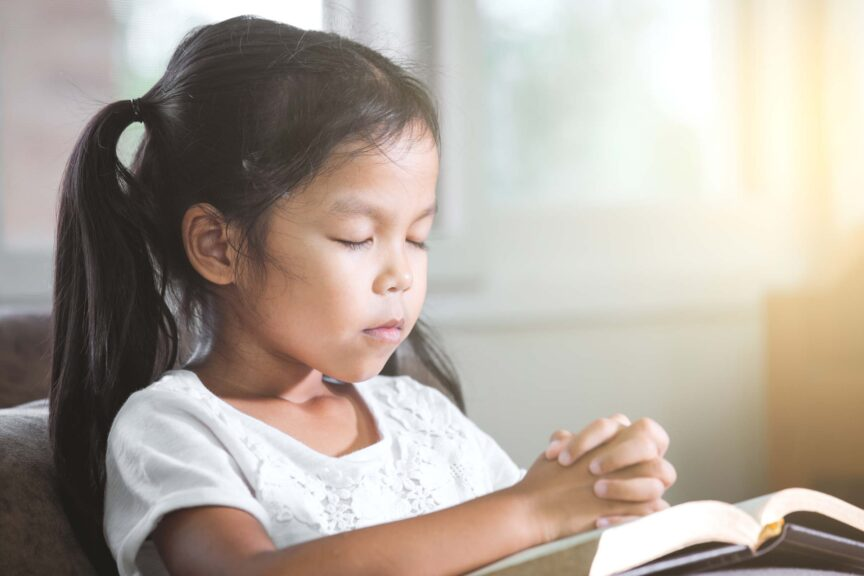 girl-closed-her-eyes-and-folded-her-hand-in-prayer-on-a-Holy-Bible