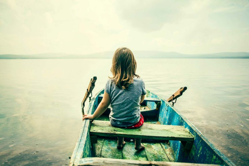 Girl sitting in boat on lake