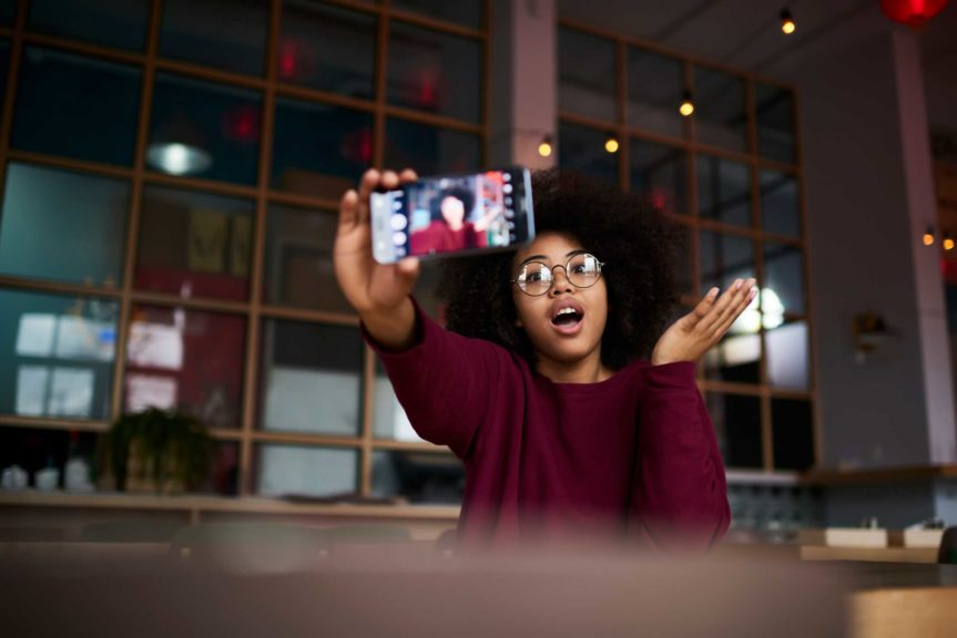 girl with curly hair in trendy glasses posing while making photo