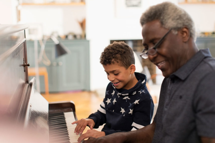 Grandfather and grandson cheerfully playing the piano