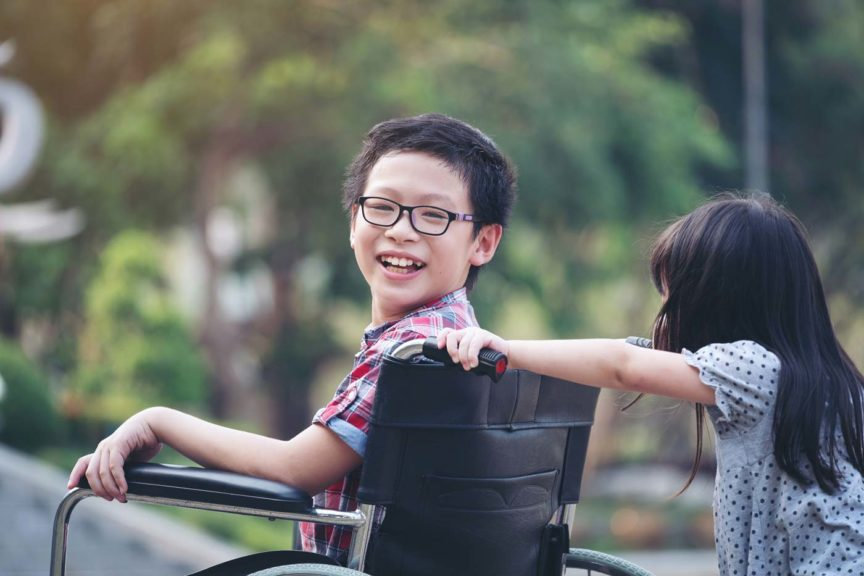 Boy in wheelchair smiling with sister