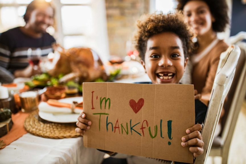 girl holding 'I'm thankful' sign and looking at camera during Thanksgiving meal with her parents
