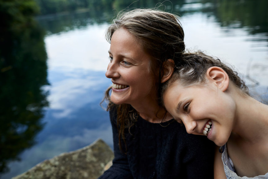 Portrait of happy mother and daughter at a lake
