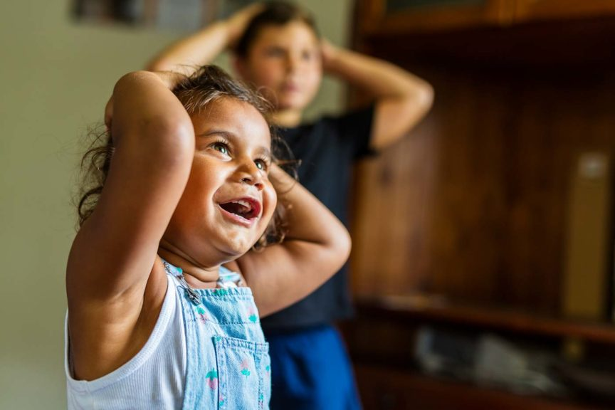 Happy Young Australian Aboriginal Girl Learning to Sing and Dance to a Song