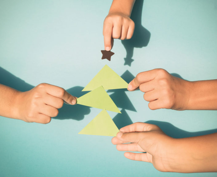 Kids hands holding paper cut out Christmas tree