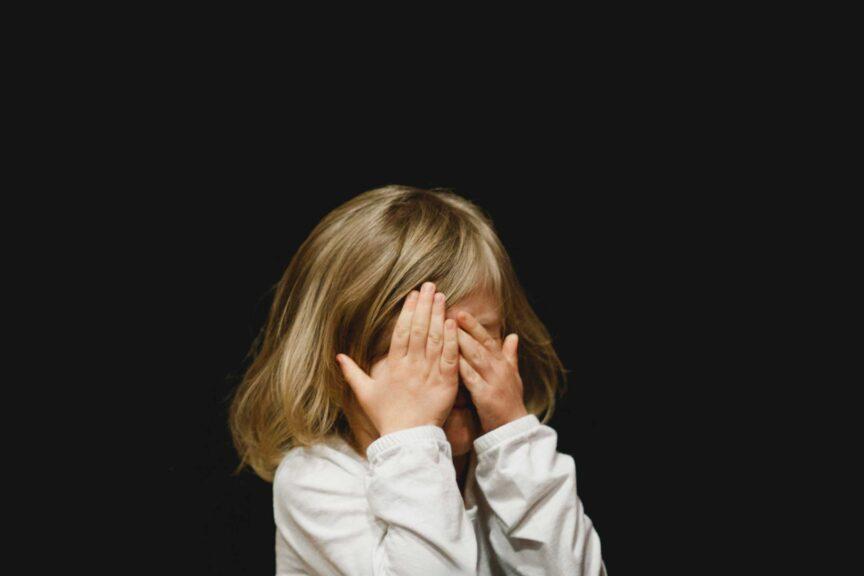 little-girl-covering-eyes-back-background