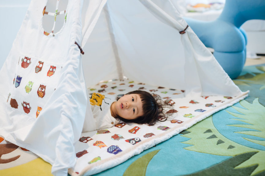 A little girl was lying in the small tent