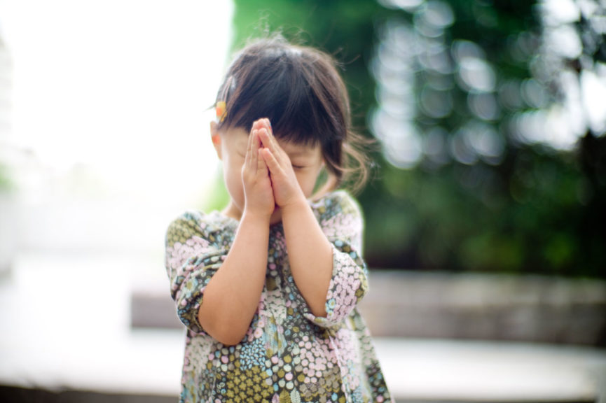 Little girl praying with hands together