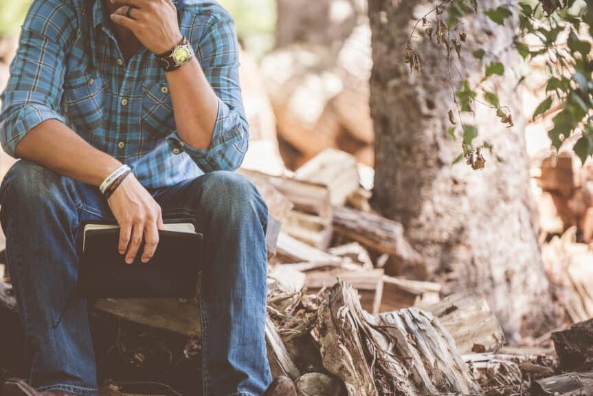 man-bible-sitting-outdoors-log