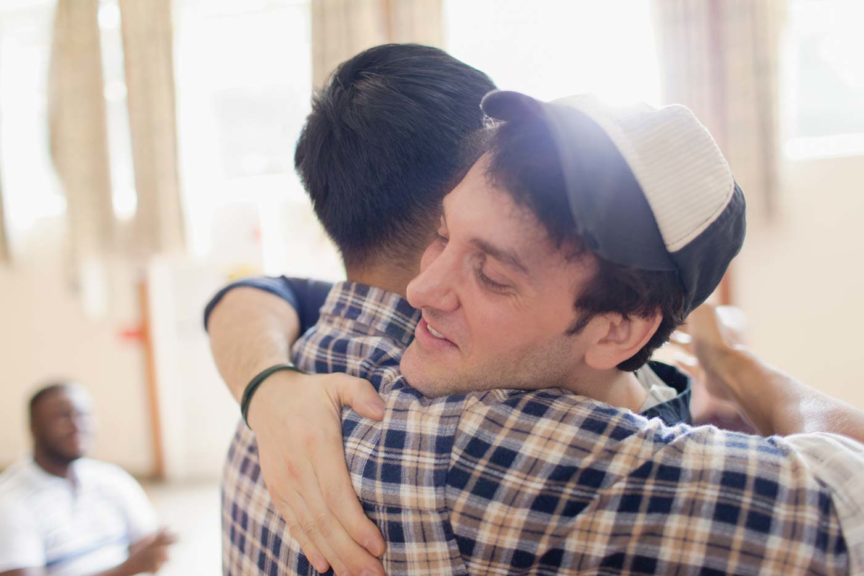 Man in hat hugging man