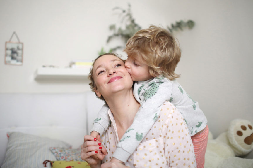 mother being kissed by child at home
