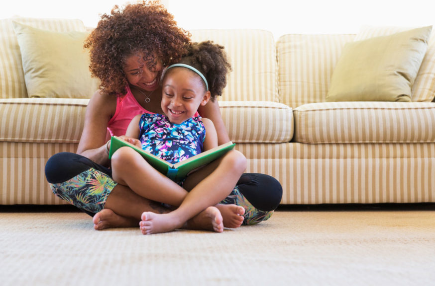 mother and daughter reading book on floor near sofa