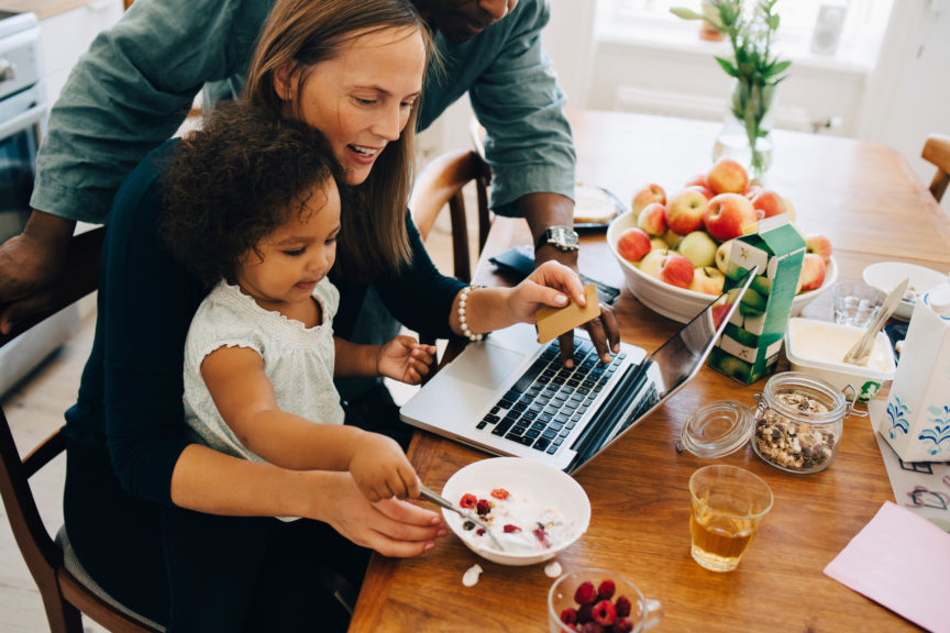 Parents shopping online on laptop while looking at daughter having breakfast in dining room