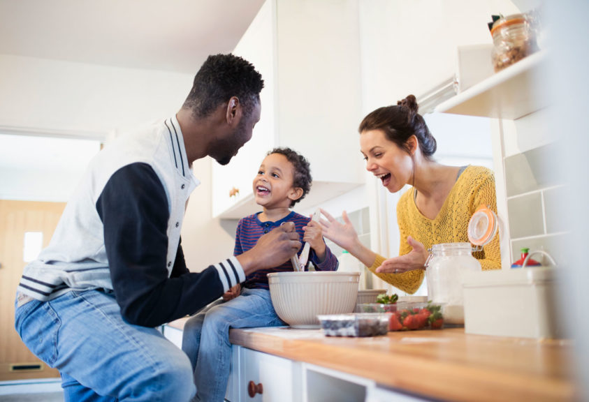 Parents and toddler son baking in kitchen