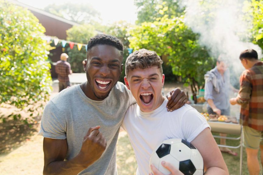 portrait-enthusiastic-men-soccerball-cheering-bbq