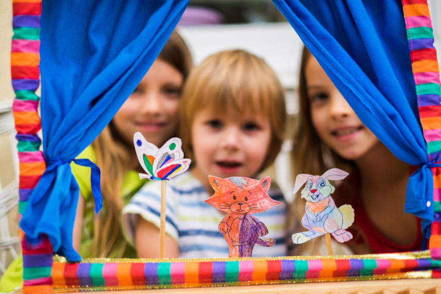 Portrait three cute children playing puppet show