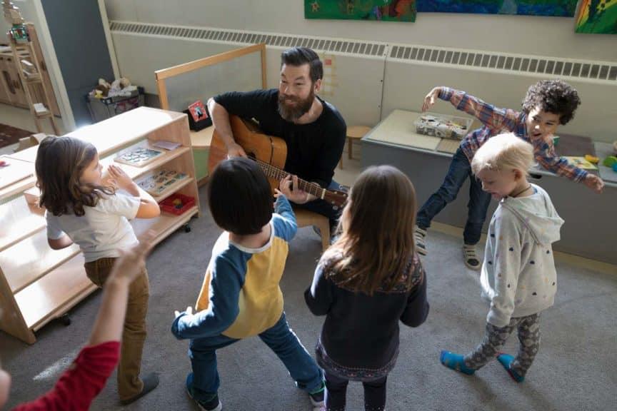 preschool-students-dancing-teacher-guitar-classroom