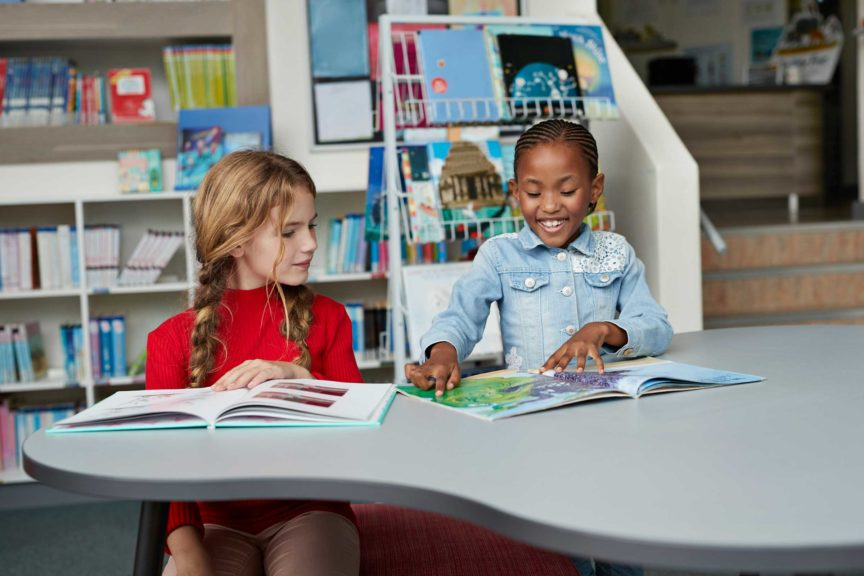 Schoolgirls laughing & reading books in school library