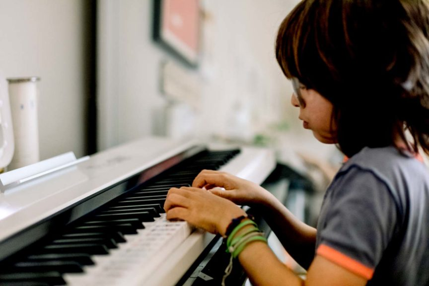 Side view of child playing on a smart piano