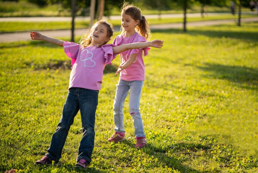 sisters-playing-in-yard-falling-back