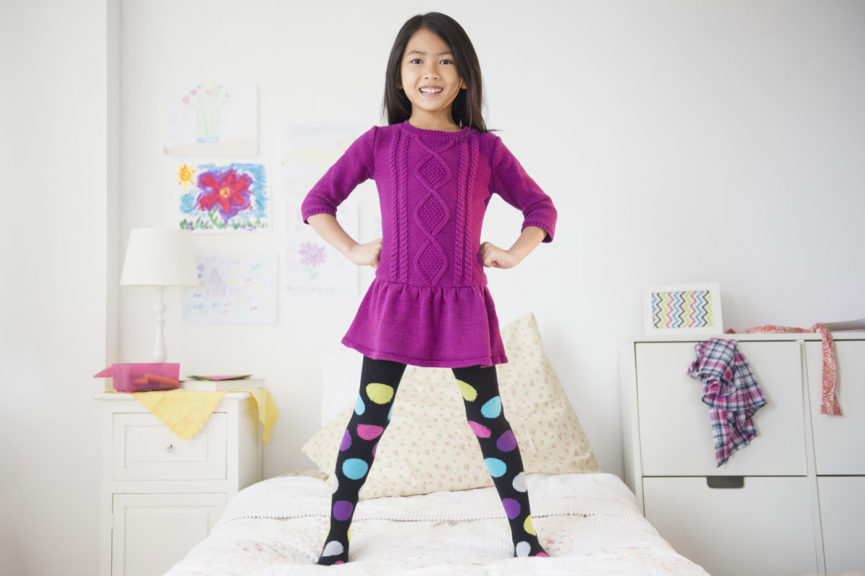Smiling girl standing on bed