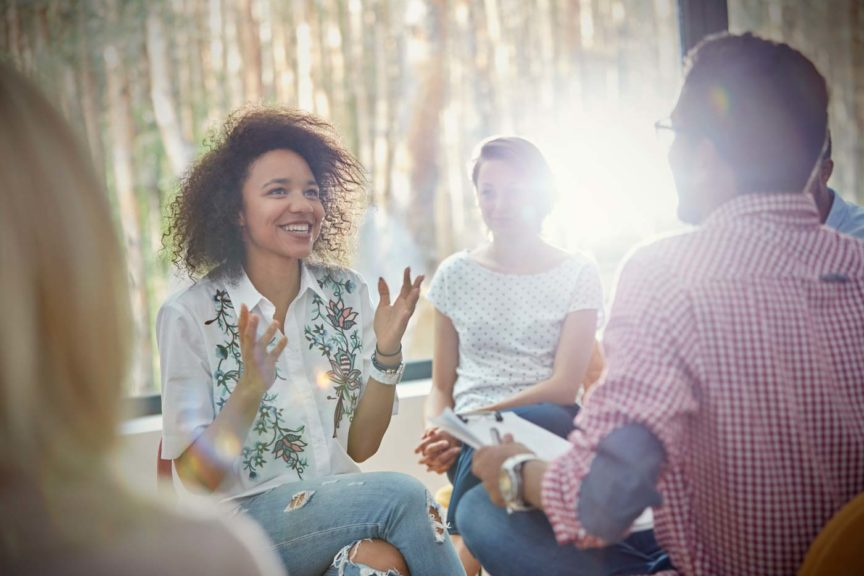 smiling-woman-talking-group-therapy-session