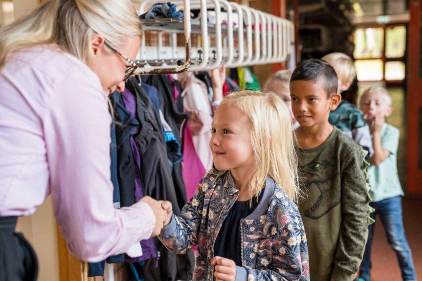 teacher greeting kids in classroom