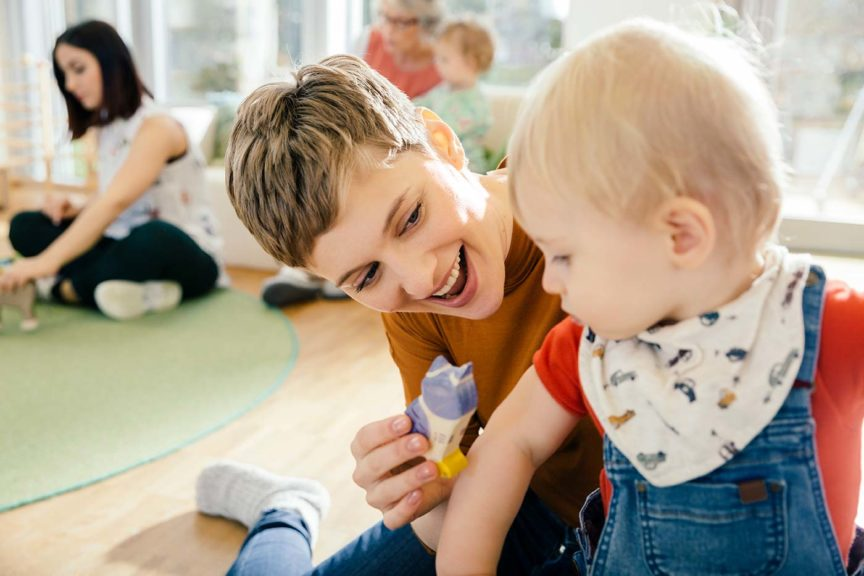 teacher playing with toddler ministry volunteers