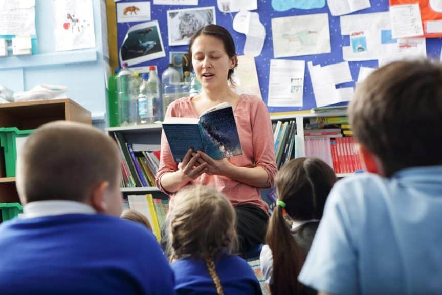 teacher reading elementary students