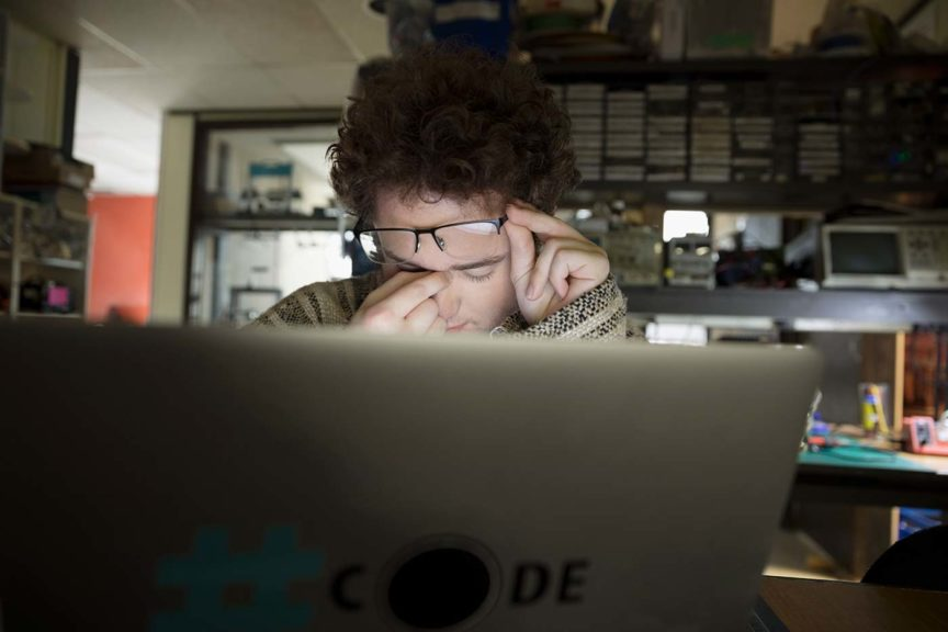 depressed teenage boy using computer
